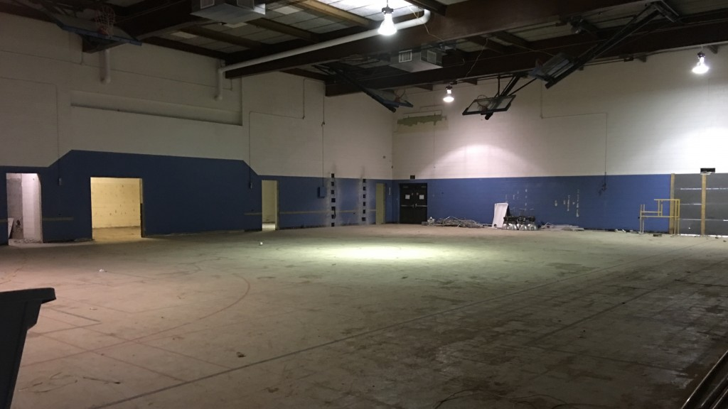 In the gym, basketball backboards remain, but bleachers and the worn plastic floor have been removed. One of the major elements of the renovation will occur behind the blue paint at left, where a larger fitness room will be installed.